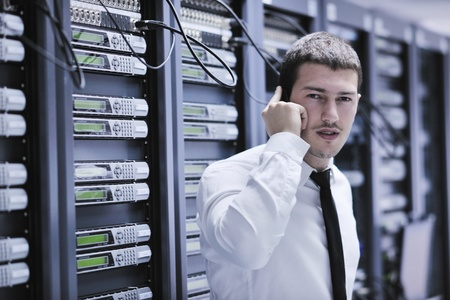 it: young business man computer science engeneer talking by cellphone at network datacenter server room asking  for help and fast solutions and services Stock Photo