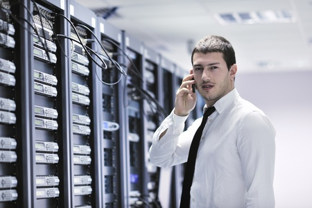 young business man computer science engeneer talking by cellphone at network datacenter server room asking  for help and fast solutions and services Stock Photo - 8437084