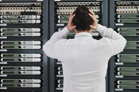 errors: business man in network server room have problems and looking for  disaster solution