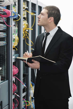 young engeneer business man with notebook  in network server room photo