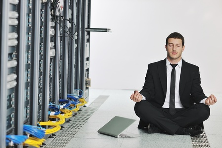 young handsome business man in black suit and tie practice yoga and relax at network server room while representing stres control concept Stock Photo - 8445729