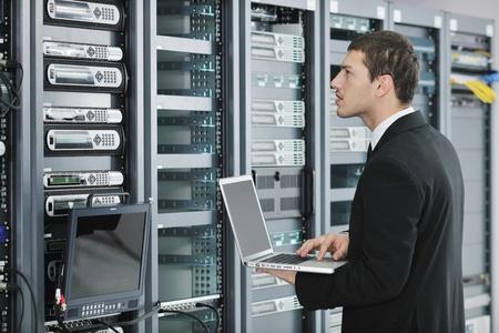 cable red: hombre de negocios de j�venes engeneer con fina aluminio moderna port�til en la sala de servidores de red