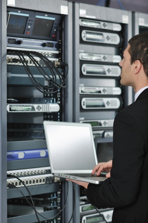 young engeneer business man with thin modern aluminium laptop in network server room Stock Photo - 8445728