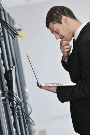 young engeneer business man with thin modern aluminium laptop in network server room Stock Photo - 8445700