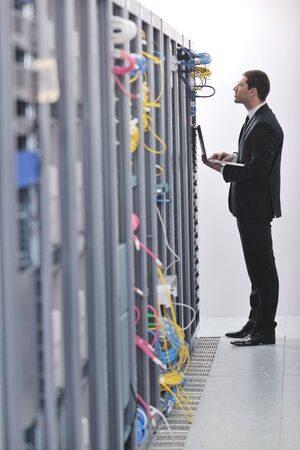 young engeneer business man with thin modern aluminium laptop in network server room Stock Photo - 8445726