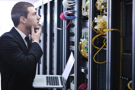 young engeneer business man with thin modern aluminium laptop in network server room Stock Photo - 8445709