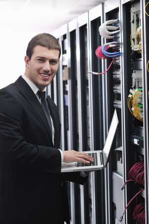 young engeneer business man with thin modern aluminium laptop in network server room Stock Photo - 8445731
