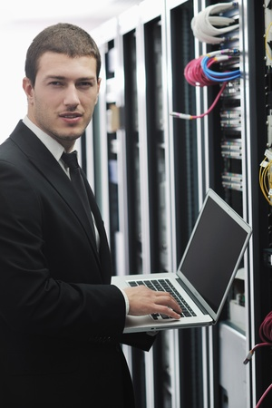 young engeneer business man with thin modern aluminium laptop in network server room Stock Photo - 8445725
