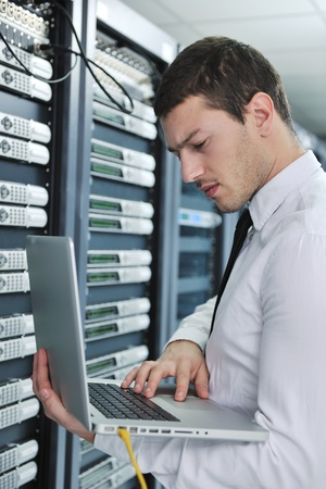 young engeneer business man with thin modern aluminium laptop in network server room Stock Photo - 8445741