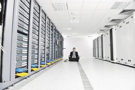 stres: young handsome business man in black suit and tie practice yoga and relax at network server room while representing stres control concept