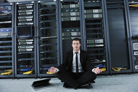 young handsome business man in black suit and tie practice yoga and relax at network server room while representing stres control concept photo