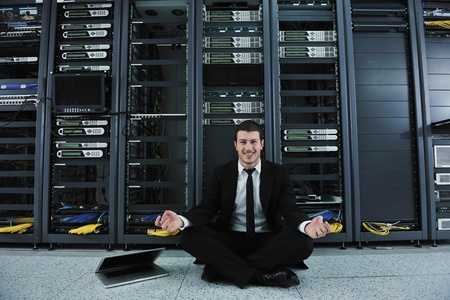 young handsome business man in black suit and tie practice yoga and relax at network server room while representing stres control concept Stock Photo - 8445759
