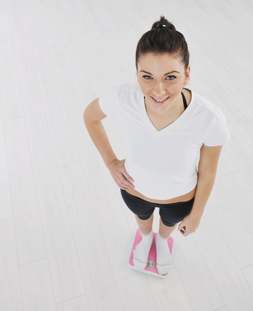 happy diet concept with young woman on pink scale at sport fitnes gym club photo