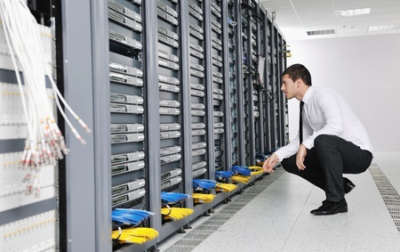 isp: young handsome business man it  engeneer in datacenter server room