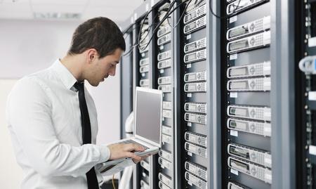 jeune homme, il engeneer d'affaires avec un ordinateur portable mince d'aluminium moderne dans la salle de serveur réseau