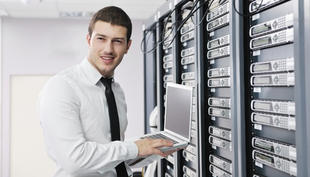 network engineer: young it  engeneer business man with thin modern aluminium laptop in network server room