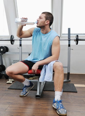 young man drink water at fitness workout training at sport club photo
