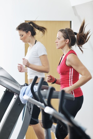 young woman exercise fitness and workout while run on track in sport club photo