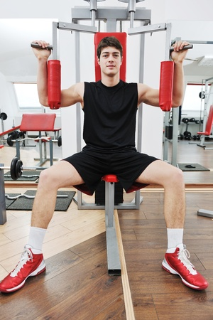 young man in fintess sport club exercise withweights and relaxing photo