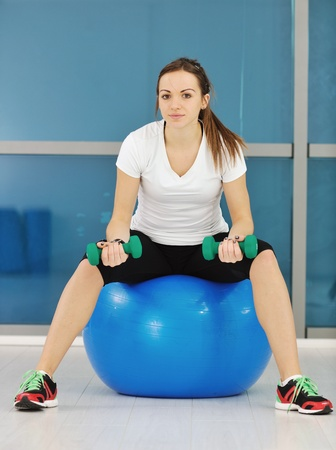 beaudiful young woman fitness workout with weights at sport club photo