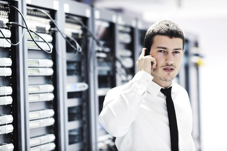 it support: young business man computer science engeneer talking by cellphone at network datacenter server room asking  for help and fast solutions and services Stock Photo