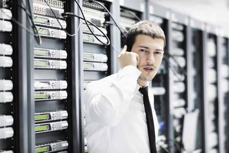 young business man computer science engeneer talking by cellphone at network datacenter server room asking  for help and fast solutions and services Stock Photo - 8758977