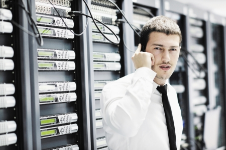 通信: ヘルプと高速なソリューションとサービスを求めるネットワーク データ センター サーバー ルームでの携帯電話によって話している若いビジネス男