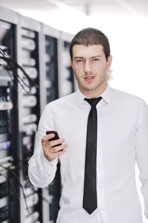 young business man computer science engeneer talking by cellphone at network datacenter server room asking  for help and fast solutions and services Stock Photo - 8767588