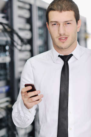 young business man computer science engeneer talking by cellphone at network datacenter server room asking  for help and fast solutions and services Stock Photo - 8772691