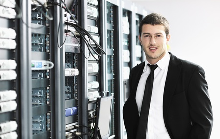 young it  engeneer business man with thin modern aluminium laptop in network server room Stock Photo - 8778196