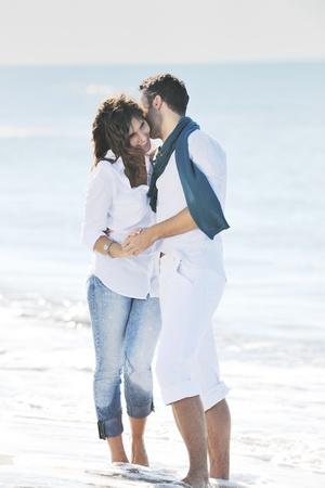 felice giovane coppia in abiti bianchi hanno romantica di ricreazione e divertimento alla bellissima spiaggia sulle vacanze
