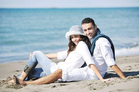 feliz pareja joven en ropa blanca tiene esparcimiento romántica y diversión en la hermosa playa de vacaciones