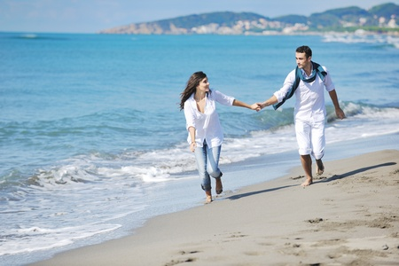 young lovers: happy young couple in white clothing  have romantic recreation and   fun at beautiful beach on  vacations Stock Photo