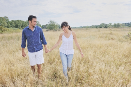 field glass: happy couple enjoying countryside picnic in long grass Stock Photo