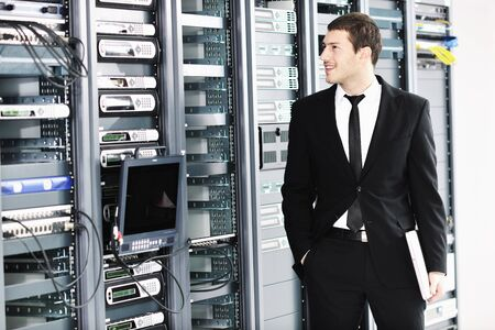 young it  engeneer business man with thin modern aluminium laptop in network server room Stock Photo - 8769449