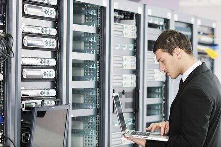 young it  engeneer business man with thin modern aluminium laptop in network server room photo