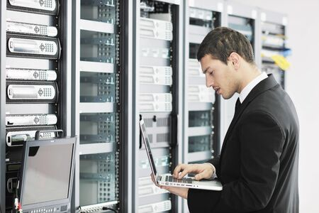 young it  engeneer business man with thin modern aluminium laptop in network server room Stock Photo - 8769439