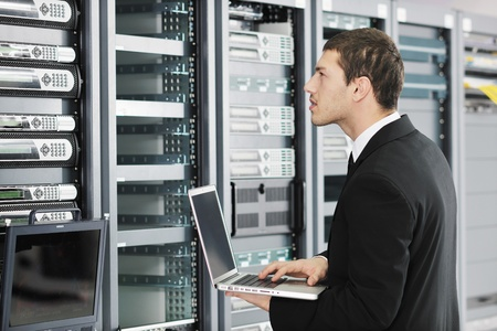 young it  engeneer business man with thin modern aluminium laptop in network server room Stock Photo - 8773893