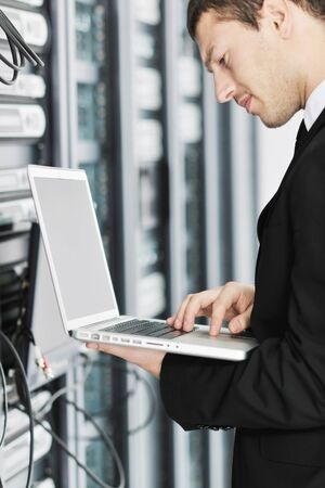 young it  engeneer business man with thin modern aluminium laptop in network server room Stock Photo - 8768795
