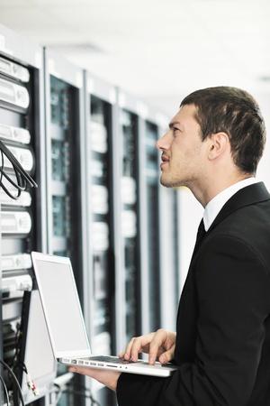 Cable network: j�venes hombre de negocios de ingeniero con delgado de aluminio moderna port�til en la sala de servidores de red Foto de archivo