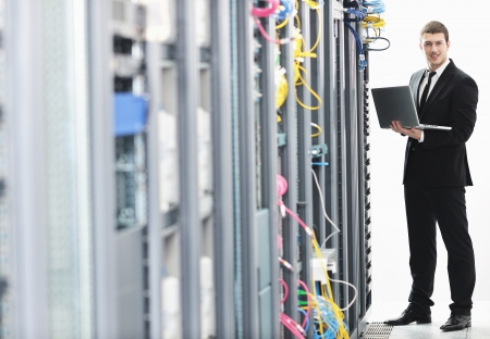 young it  engeneer business man with thin modern aluminium laptop in network server room Stock Photo - 8769095