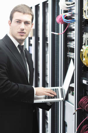 young it  engeneer business man with thin modern aluminium laptop in network server room Stock Photo - 8769435