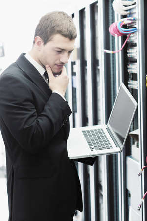 young it  engeneer business man with thin modern aluminium laptop in network server room Stock Photo - 8769436