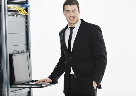 network server: young it  engeneer business man with thin modern aluminium laptop in network server room