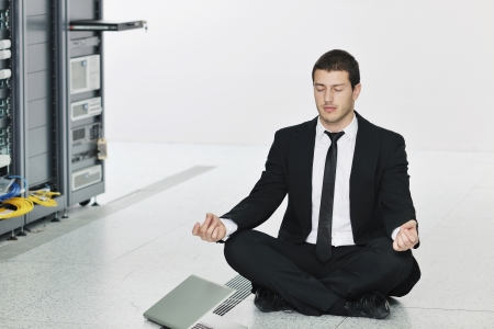 young handsome business man in black suit practice yoga and relax at network server room while representing stress control concept photo