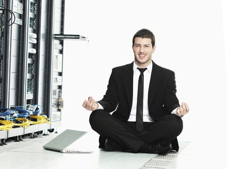 stres: young handsome business man in black suit practice yoga and relax at network server room while representing stress control concept