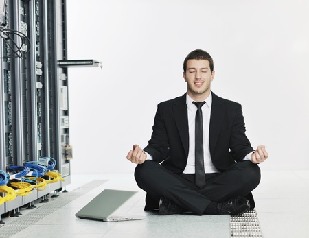backups: young it  engeneer business man with thin modern aluminium laptop in network server room