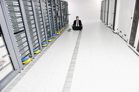 young handsome business man in black suit practice yoga and relax at network server room while representing stress control concept Stock Photo - 8773886