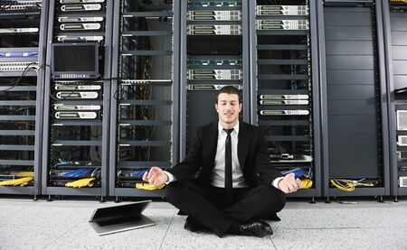 racks: young it  engeneer business man with thin modern aluminium laptop in network server room