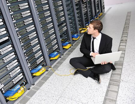 young it  engeneer business man with thin modern aluminium laptop in network server room Archivio Fotografico - 8773896